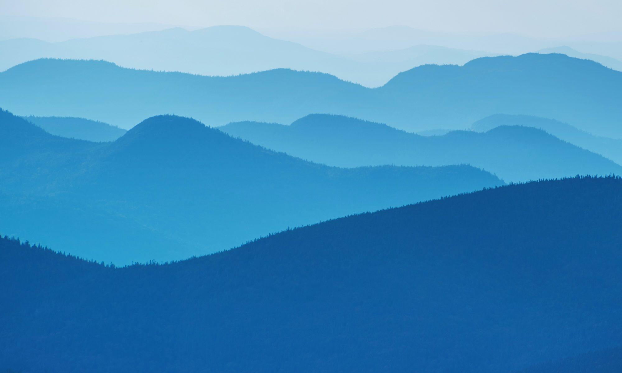 Kuvituskuva sinisestä maisemasta. Maiseman aaltomaiset muodot samanlaiset kuin Mediakasvatuslinjausten kannessa