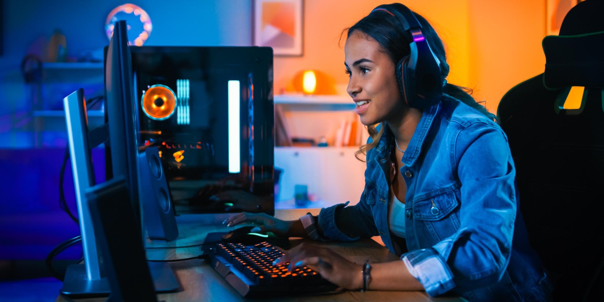 Nuori nainen tai tyttö pelaa tietokoneella kuulokkeet päässään